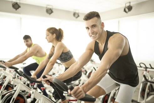 People exercising on spinning bikes in gym - JASF01398