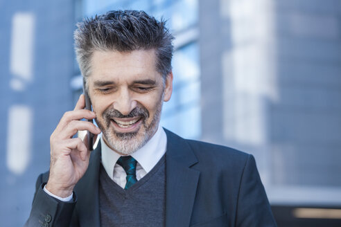 Smiling businessman outdoors on cell phone - TCF05218