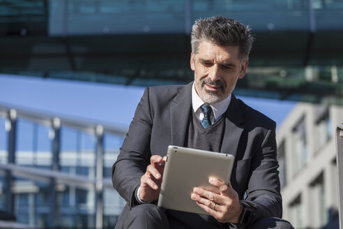Businessman outdoors using tablet - TCF05224
