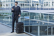 Businessman with cell phone standing with suitcase on bridge - TCF05230