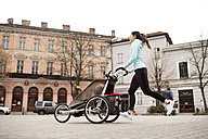 Mother running with child in stroller in the city - HAPF01203