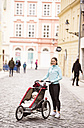 Mother in sportswear with child in stroller in the city - HAPF01206