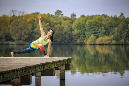 Woman practicing yoga on jetty at a lake - VTF00574