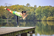 Woman practicing yoga on jetty at a lake - VTF00577