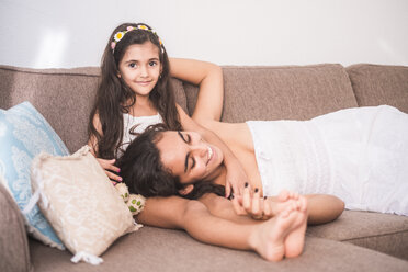 Teenage girl and her little sister lying on couch - SIPF01168