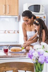 Teenage girl and her little sister in kitchen cutting a cake - SIPF01174