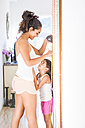 Teenage girl measuring her little sister - SIPF01183