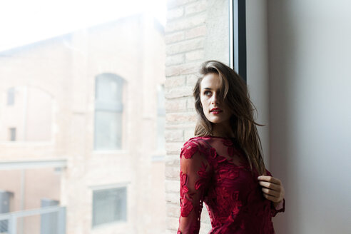 Beautiful young woman wearing red dress at a window - VABF00920