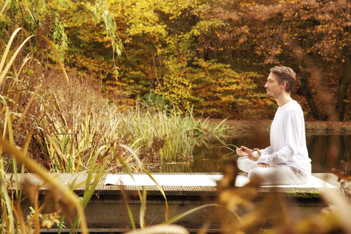 Man practicing yoga on a jetty at a pond in autumn - MFRF00831