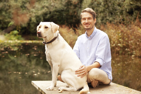 Man with dog on a jetty at a pond in autumn - MFRF00837
