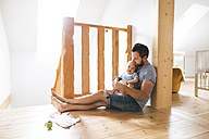 Father sitting on floor with baby at home - HAPF01220