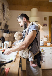 Happy father with baby in baby carrier doing the dishes - HAPF01223