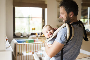 Happy father with baby in baby carrier at home - HAPF01226