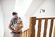 Father with baby in baby carrier walking upstairs - HAPF01229