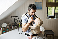 Father with baby in baby carrier brushing his teeth - HAPF01232