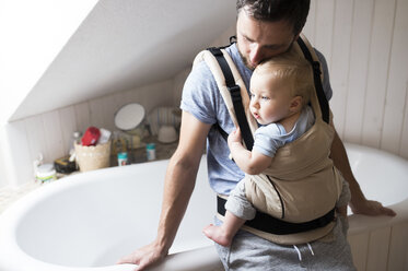 Father with baby in baby carrier in bathroom - HAPF01235
