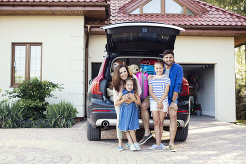 Happy family standing in front of car packed for vacation - WEST22306