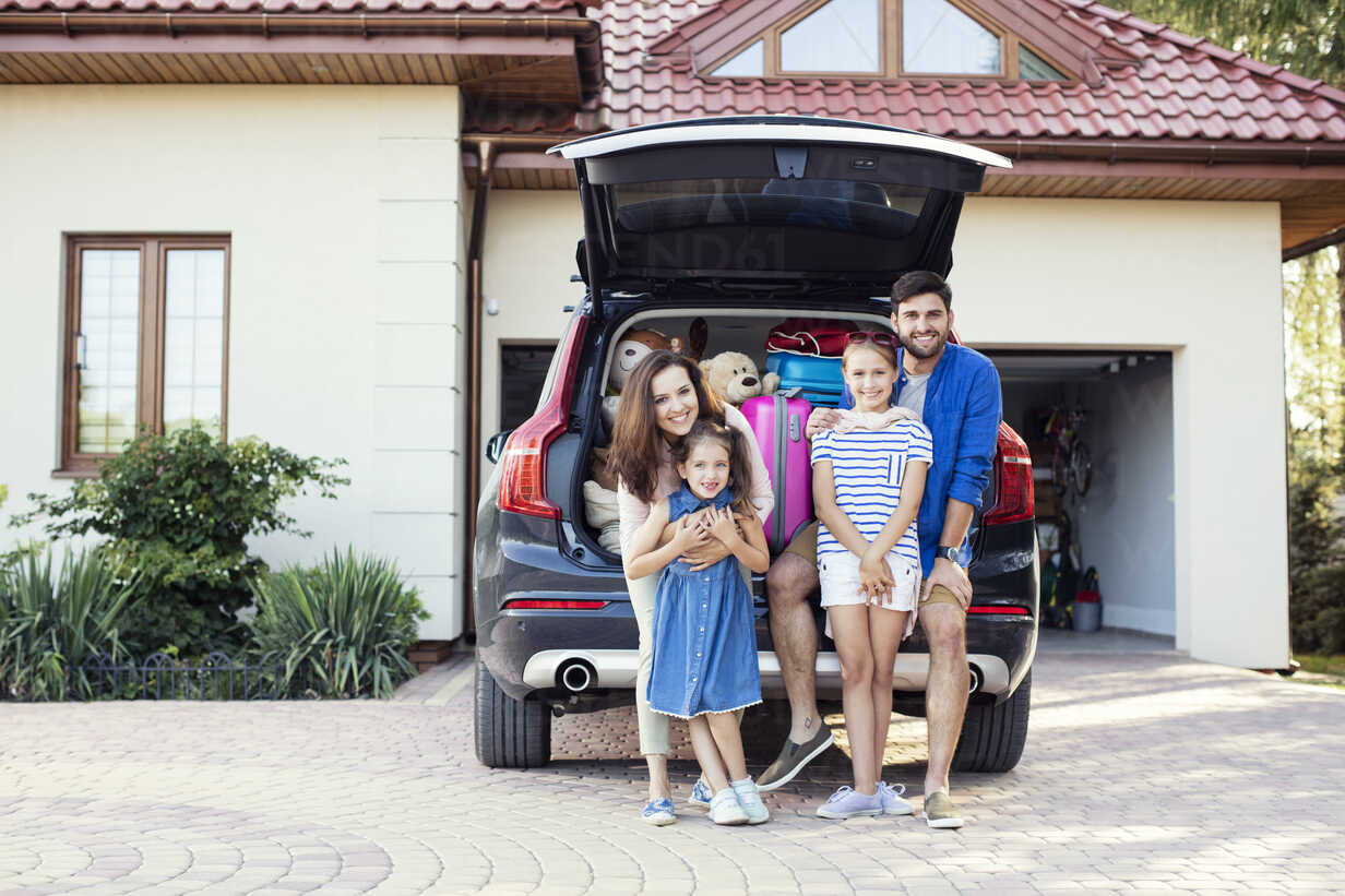 Happy family standing in front of car packed for vacation - WEST22306 - Fotoagentur WESTEND61/Westend61