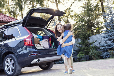 Mother and daughter embracing in front of their car - WEST22321