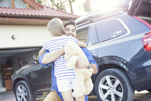 Father and daughter embracing in front of their car - WEST22324