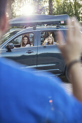 Father waving mother and daughter goodbye, as they drive off - WEST22327