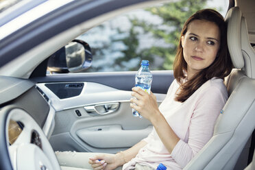 Woman sitting in car, holding bottle of water - WEST22333