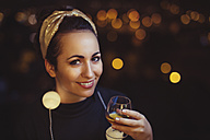 Portrait of smiling woman with drink wearing golden hair-band - LCUF00085