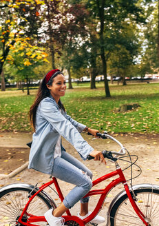 Smiling young woman riding a bike in a park - MGOF02697