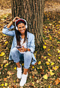 Young woman listening to music with her smartphone in a park in autumn - MGOF02706