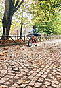 Happy young woman riding a bike in a park - MGOF02709