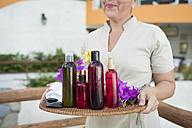 Massage therapist holding a tray with oil, lotion, and towels at a luxury vacation resort - ABAF02105
