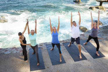 Instructor helping group doing yoga at ocean front - ABAF02117