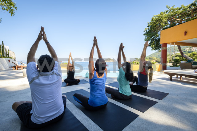 Yoga group with teacher exercising at ocean front villa - ABAF02120 - André Babiak/Westend61