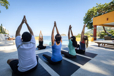 Yoga group with teacher exercising at ocean front villa - ABAF02120