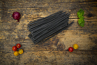 Uncooked Spaghetti al Nero di Seppia, red onion, basil leaves and tomatoes on wood - LVF05716