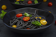 Bowl of Spaghetti al Nero di Seppia with tomatoes and basil leaves, close-up - LVF05719