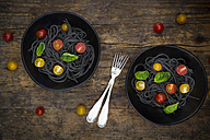Two bowls of Spaghetti al Nero di Seppia with tomatoes and basil leaves - LVF05722