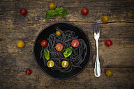 Bowl of Spaghetti al Nero di Seppia with tomatoes and basil leaves - LVF05725