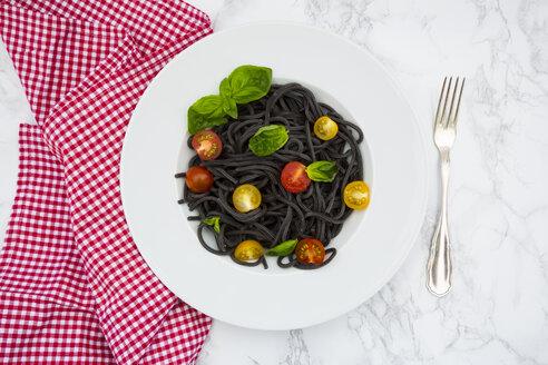 Plate of Spaghetti al Nero di Seppia with tomatoes and basil leaves - LVF05728