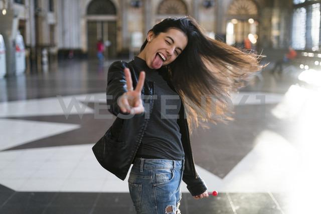 Portrait of exuberant young woman with lollipop in station concourse - KKAF00192 - Kike Arnaiz/Westend61