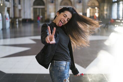 Portrait of exuberant young woman with lollipop in station concourse - KKAF00192