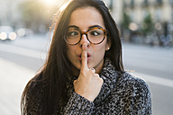Portrait of young woman with glasses pulling faces - KKAF00195