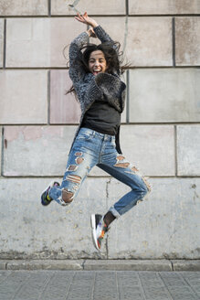Portrait of exuberant young woman jumping around - KKAF00198
