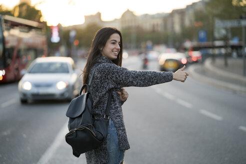 Smiling young woman hitchhiking on urban street - KKAF00201