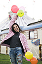 Happy young woman holding balloons outdoors - KKAF00204