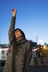 Enthusiastic young woman outdoors at night - KKAF00210