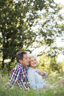 Senior couple relaxing together on a meadow - HAPF01242