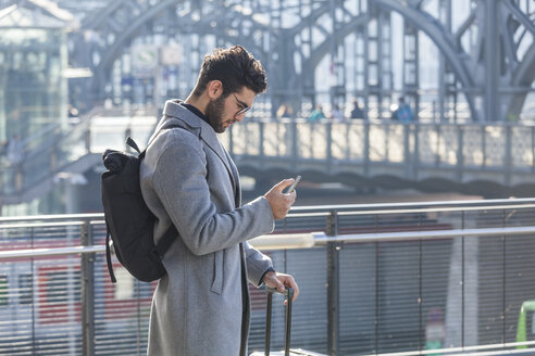 Businessman with baggage looking at cell phone at train station - TCF05236