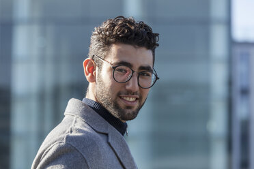 Portrait of smiling young businessman with beard and spectacles - TCF05239