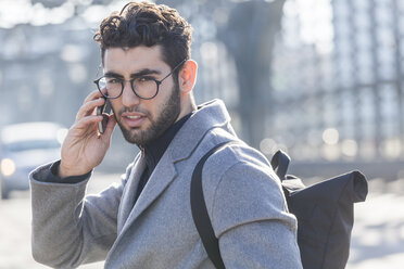 Portrait of young businessman with backpack on the phone - TCF05245